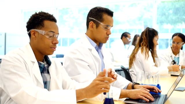Diverse chemists or chemistry students work on scientific experiment Mid adult Hispanic scientist or chemistry student records chemistry experiment findings on a laptop while his lab partner or colleague conducts the experiment by dropping liquid from a beaker into a test tube. The men are wearing safety glasses and lab coats. Their colleagues are working in the background. beaker stock videos & royalty-free footage