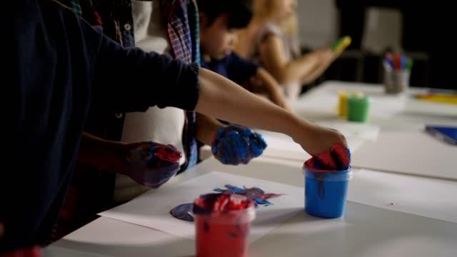 vídeos de stock, filmes e b-roll de diversas crianças com mãos de tinta na aula de arte - professor de pré escola