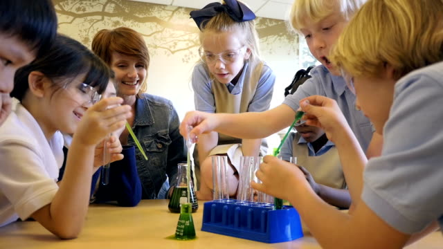 diverse class of students in private elementary school doing chemistry science experiment - chemistry stock videos and b-roll footage