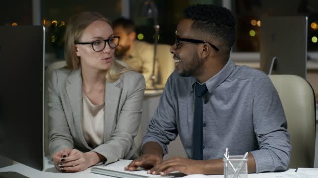 stockvideo's en b-roll-footage met diverse collega's werken laat in de avond - flirten