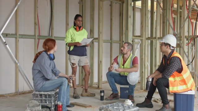 Diverse construction workers on the coffee break Diverse construction workers sitting down having a coffee break while manager organising about next jobs at construction site. occupational safety and health stock videos & royalty-free footage