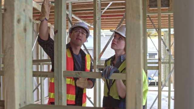 diverse construction workers talking about the next job to do - apprendista video stock e b–roll