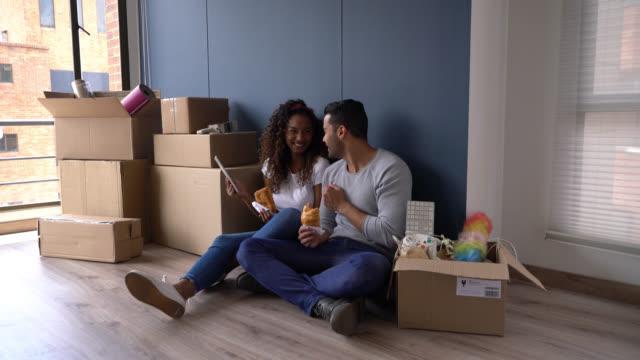 olika par tar en paus efter att flytta lådor till sitt nya hem äta croissanter och titta på något på tablett - flyttlådor bildbanksvideor och videomaterial från bakom kulisserna