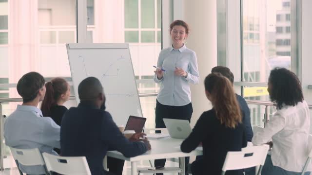 vidéos et rushes de divers employés et entraîneur fémininlèvent la main à la formation d'affaires - workshop