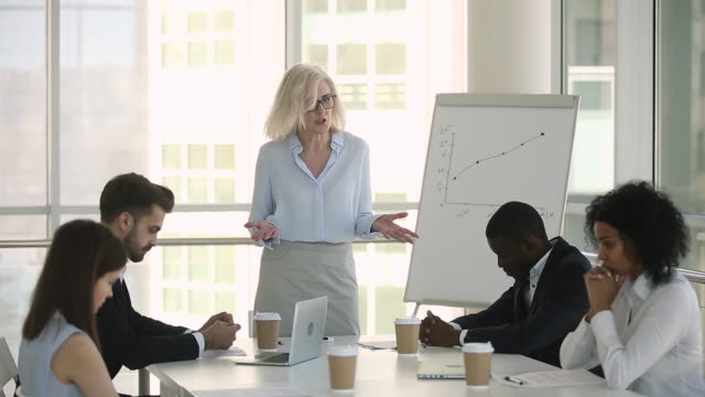 Diverse employees sitting at table scolded by irritated female boss