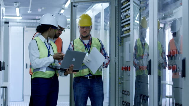 Diverse engineers with papers working in control center between racks