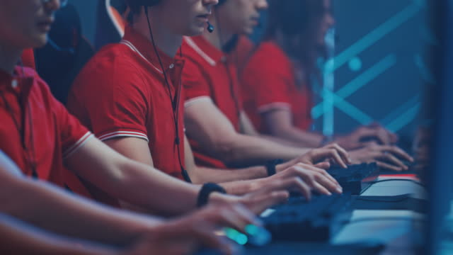 diverse esport team of pro gamers begin play in video game on a championship, put on headsets to talk. stylish neon cyber games arena. online streaming of tournament event. close-up shot - competizione video stock e b–roll