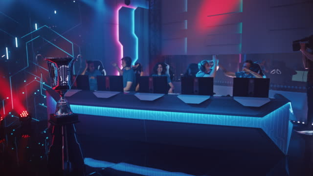 diverse esport team of pro gamers play in mock-up rpg strategy video game and win championship, happily celebrate with high-fives. neon lights. online streaming of tournament. moving dolly shot - współzawodnictwo wydarzenia filmów i materiałów b-roll