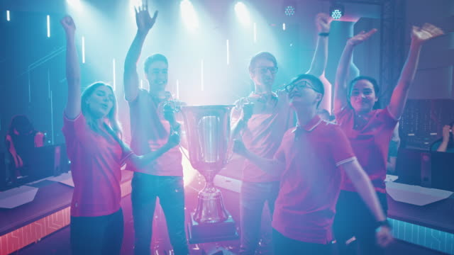 vídeos de stock e filmes b-roll de diverse esport team winner of the video games tournament celebrates victory cheering and lifting trophy in big championship arena. cyber gaming event with gamers and fans. elevating slow motion shot - campeonato
