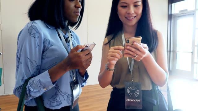 olika kvinnliga konferensdeltagare dela kontaktinformation - affärskonferens bildbanksvideor och videomaterial från bakom kulisserna