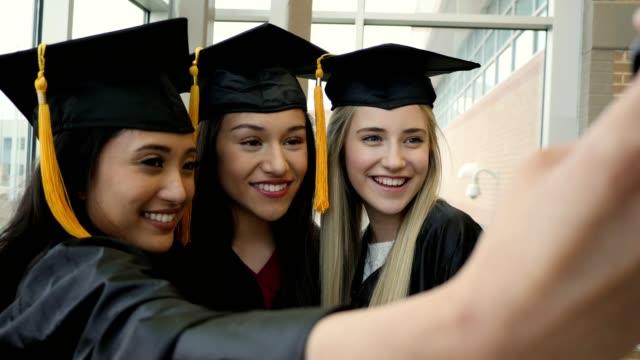 diverse female friends take selfies after graduation - celebrazione della laurea video stock e b–roll