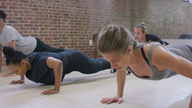 vielfältige fitness-klasse macht liegestütze - fitnesskurs stock-videos und b-roll-filmmaterial