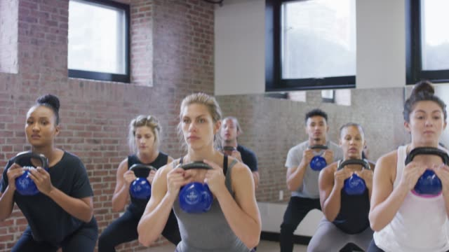 Diverse fitness class doing squats with kettle bells video