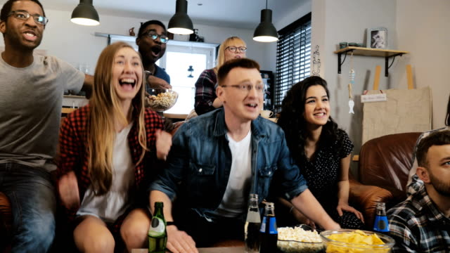 Diverse football fans get wild celebrating win 4K slow motion. Happy multi ethnic friends watching sports on TV. Emotion video