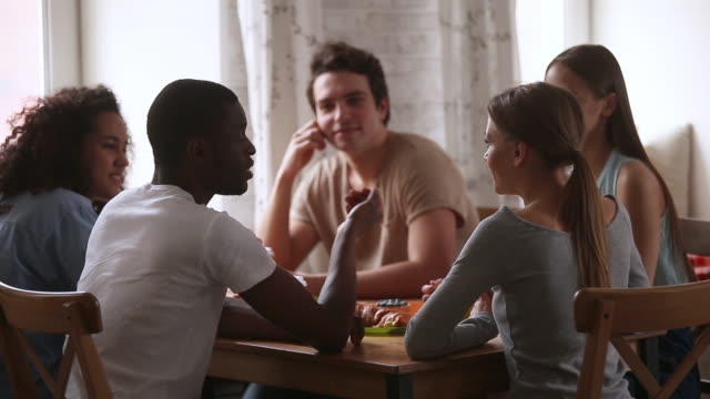 Diverse friends gathered together focus on speaking black guy