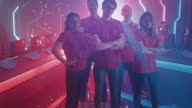 istock Diverse Gamers Esport Team Steps forward on a Stage Ready to Win Video Games Tournament, Posing at Tough Guys and Girls. Stylish Neon Championship Arena for Online Streaming of Cyber Games 1262617304