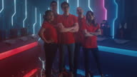 istock Diverse Gamers Esport Team Steps forward on a Stage Ready to Win Video Games Tournament, Posing at Tough Guys and Girls. Stylish Neon Championship Arena for Online Streaming of Cyber Games 1262618610