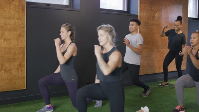 Diverse group doing lunges Diverse group of young adults doing lunges in a fitness studio cross training stock videos & royalty-free footage