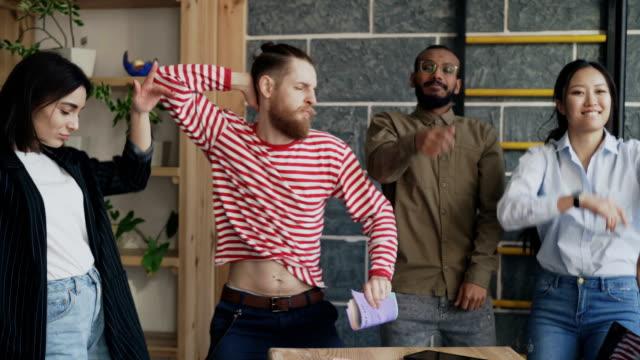 多様なグループ男女スタート アップ ビジネス チームが楽しい近代的なオフィスにダンスとプロジェクトの成功を祝う ビデオ