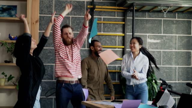 多様なグループ男女スタート アップ ビジネス チームは楽しくモダンなオフィス書類を投げるとプロジェクトの成功を祝うパーティーを踊る ビデオ