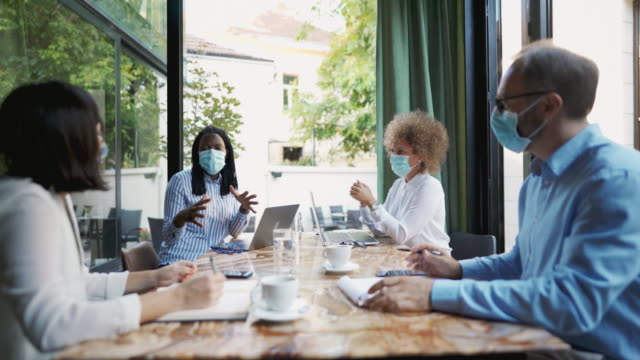 Diverse group of business people having a meeting at the coffee shop while wearing protective masks during the coronavirus pandemic