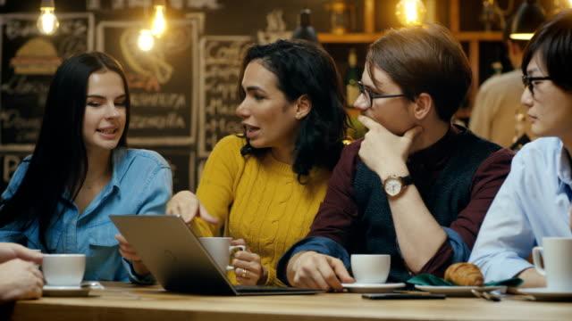 stockvideo's en b-roll-footage met diverse groep van collega's heeft businesslunch aan de bar / restaurant, zij denken over het oplossen van problemen en laptopcomputer gebruiken. mooie jonge mensen in stijlvolle inrichting. - collega