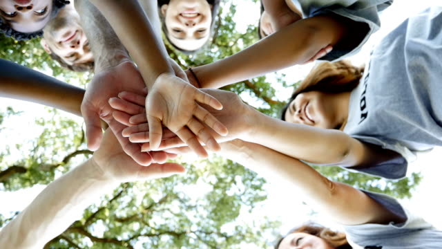 Diverse group of community volunteers with hands in a huddle outdoors