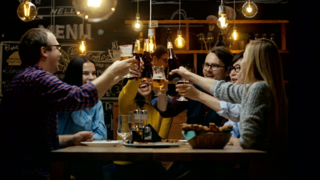 diverse group of friends celebrate with a toast and clink raised glasses with various drinks in celebration. beautiful young people have fun in the stylish bar/ restaurant. - toast filmów i materiałów b-roll