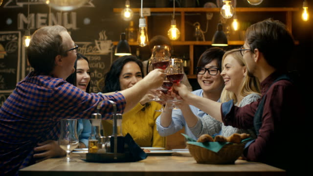 Diverse Group of Friends Celebrate with a Toast and Clink Raised Wine Glasses in Celebration. Beautiful Young People Have Fun in the Stylish Bar/ Restaurant. video