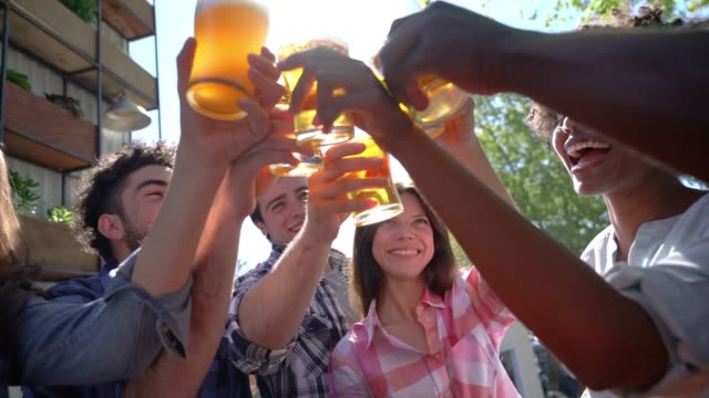 diverse group of friends enjoying happy hour at an outdoor bar and making a toast very happy - birra video stock e b–roll