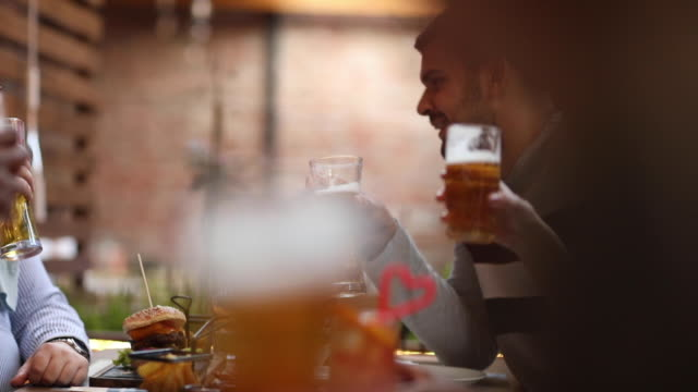 Diverse group of friends sitting outdoors in pub and eating video