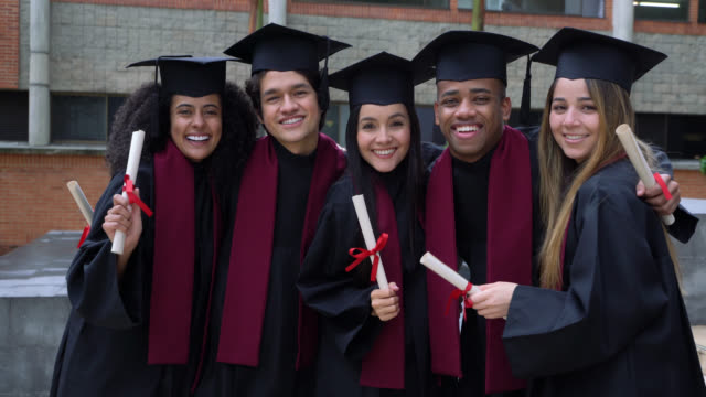 Diverse group of friends smiling at camera celebrating after their graduation ceremony Diverse group of friends smiling at camera celebrating after their graduation ceremony from college diploma stock videos & royalty-free footage