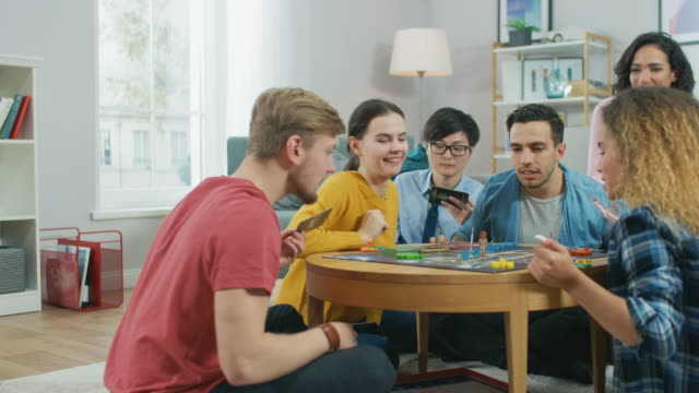 Diverse Group of Guys and Girls Playing in a Strategic Board Game with Cards and Dice. Reading Cards and Laughing. Friends Having Fun. Cozy Living Room in a Daytime