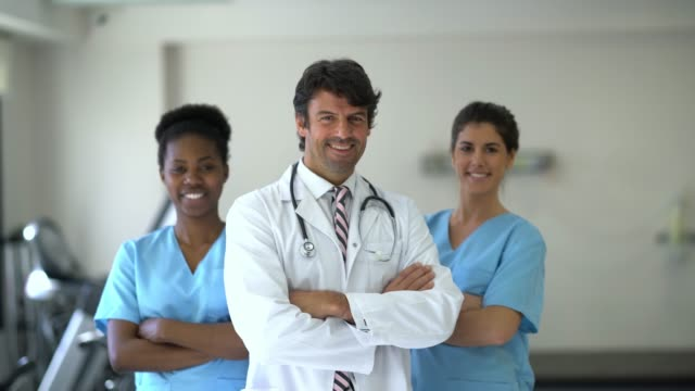 Diverse group of healthcare professionals at a physical recovery clinic looking at camera smiling Diverse group of healthcare professionals at a physical recovery clinic looking at camera smiling with arms crossed physical position stock videos & royalty-free footage