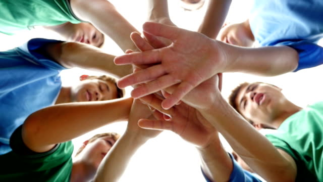 stockvideo's en b-roll-footage met diverse groep van junior high school voetbalspelers met handen in een huddle - kindertijd