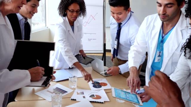 heterogene gruppe von männlichen und weiblichen angehörigen der gesundheitsberufe mit medizinischen vertriebsmitarbeiter treffen - konferenzraum videos stock-videos und b-roll-filmmaterial