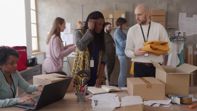 vídeos de stock e filmes b-roll de diverse group of people arranging customers orders for drop shipping - arranjo