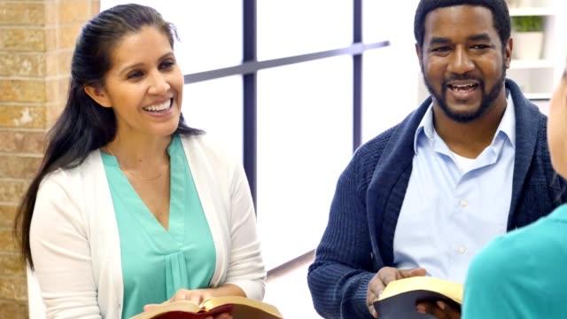 Un groupe diversifié de personnes participent à l'étude de la Bible à l'église - Vidéo