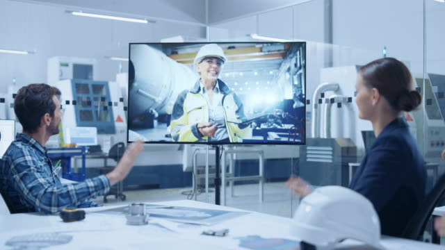 diverse group of specialists, managers in the factory office meeting room, have conference video call with factory chief female engineer, she talks about production growth, uses tablet computer - video di protezione video stock e b–roll