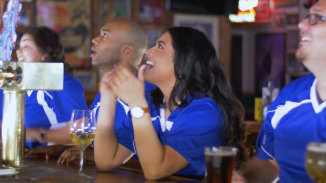 Diverse group of sports fans cheering at the bar A diverse group of young adult sports fans watching the game at the bar touchdown stock videos & royalty-free footage