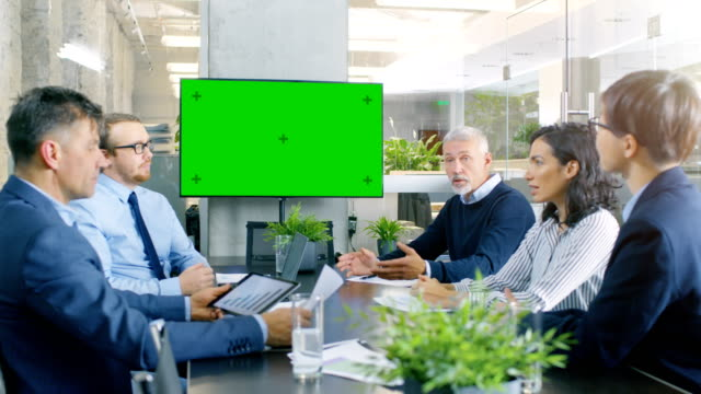 diverse group of successful business people in the conference room with  green screen chroma key tv on the wall.  they work on a company's growth, share charts and statistics. - wyprzedaż filmów i materiałów b-roll