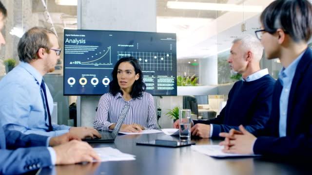 heterogene gruppe von erfolgreichen geschäftsleuten im konferenzraum des unternehmens diskutieren. sie arbeiten an einem unternehmen wachstum, anteil diagramme und statistiken. - weibliche führungskraft stock-videos und b-roll-filmmaterial