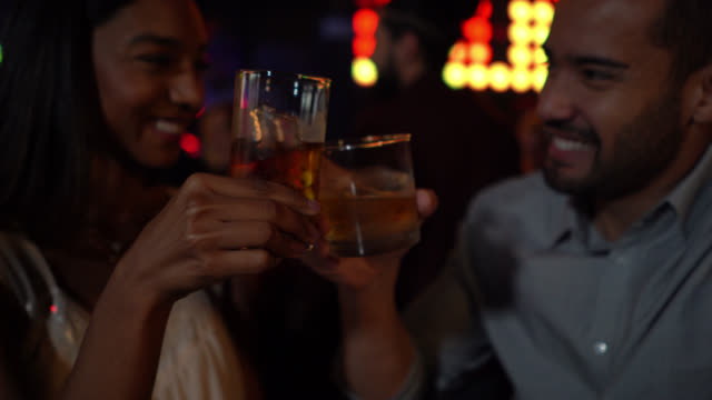 Diverse happy couple in a bar toasting with whiskey smiling and enjoying