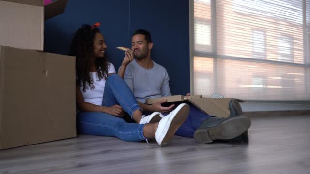 olika lyckliga paret tar en paus från förpackning lådor sitter på golvet dela en pizza - flyttlådor bildbanksvideor och videomaterial från bakom kulisserna