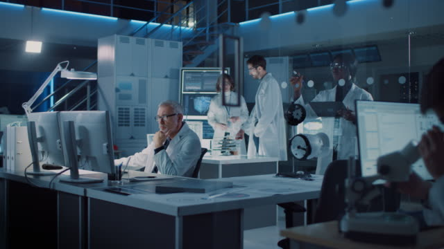 diverse international team of industrial scientists and engineers wearing white coats working on heavy machinery design in research laboratory. professionals using computers and talking - laboratorio video stock e b–roll