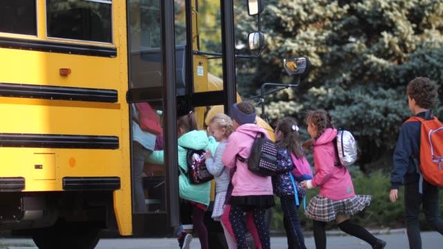 vídeos y material grabado en eventos de stock de diversos alumnos alegres que se apresuran a entrar en el autobús escolar - autobuses escolares