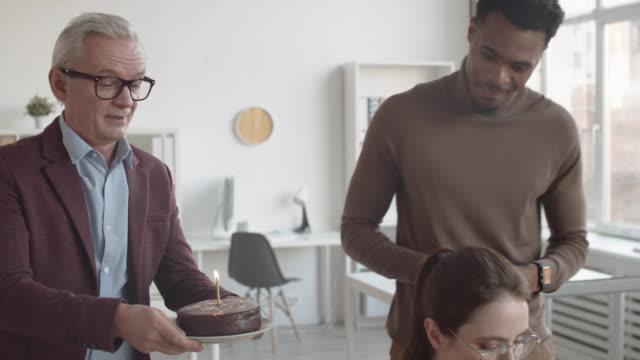 vídeos y material grabado en eventos de stock de diversos colegas masculinos sorprendentes jovencita con pastel de cumpleaños en el trabajo - aniversario