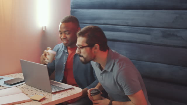 Diverse Male Coworkers Drinking Coffee and Discussing Project on Laptop