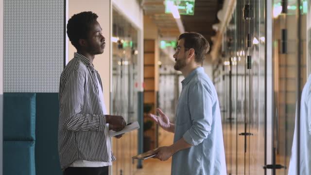 diverse männliche partner sprechen handschütteln stehend im büroflur - dankbarkeit stock-videos und b-roll-filmmaterial