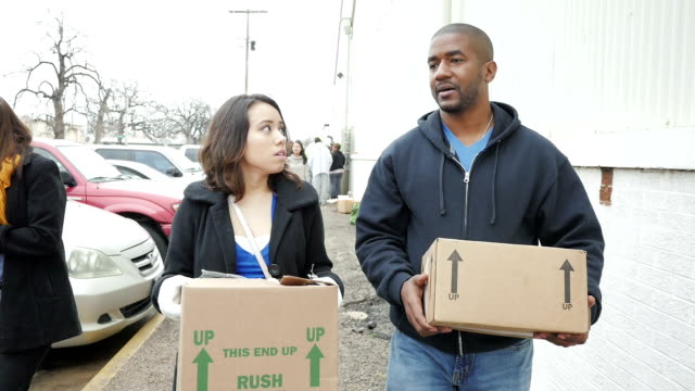 Diverse man and woman carrying boxes of donated food after waiting in line at food bank on cold day video